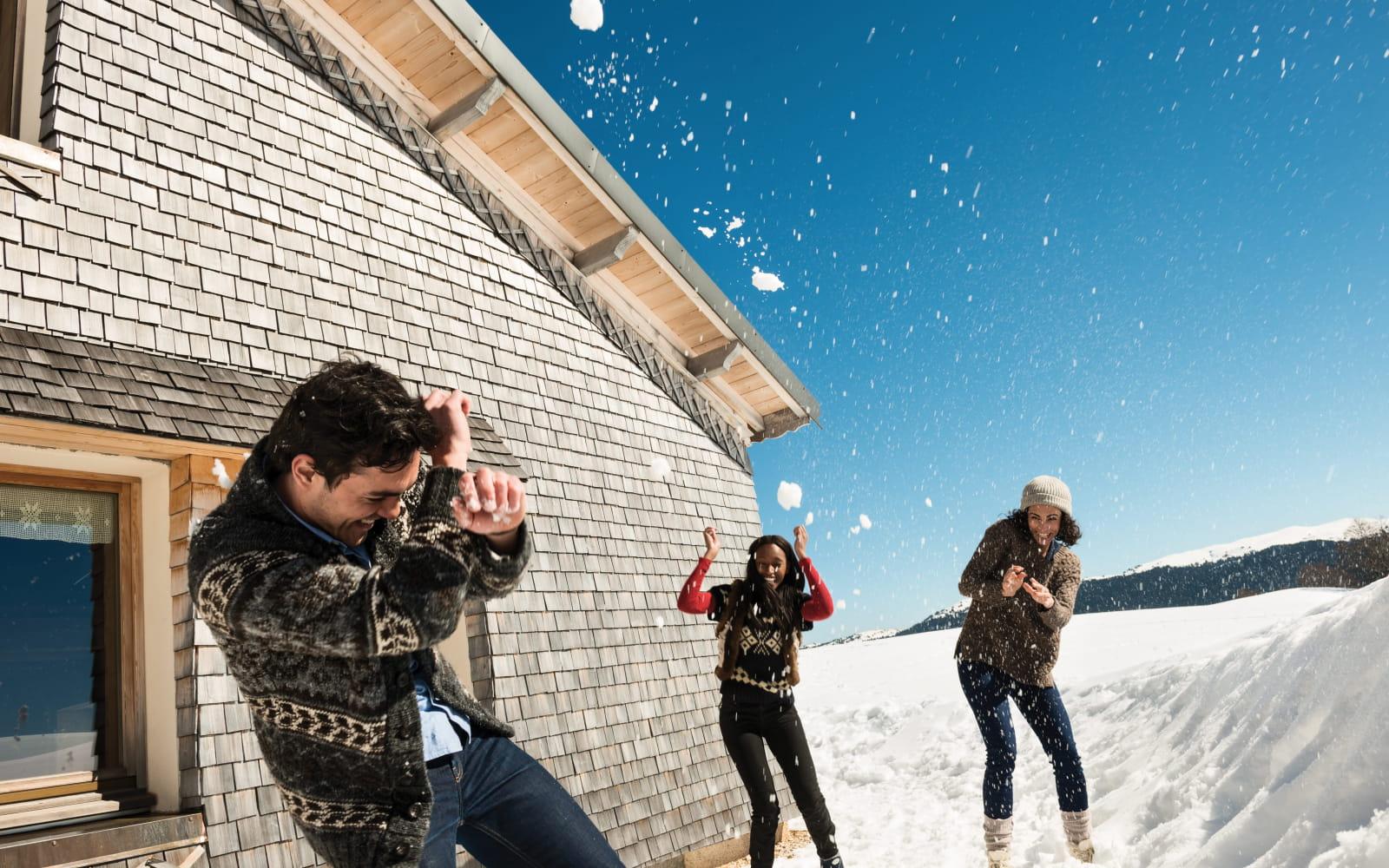 Bataille de boules de neige devant un chalet traditionnel à tavaillons