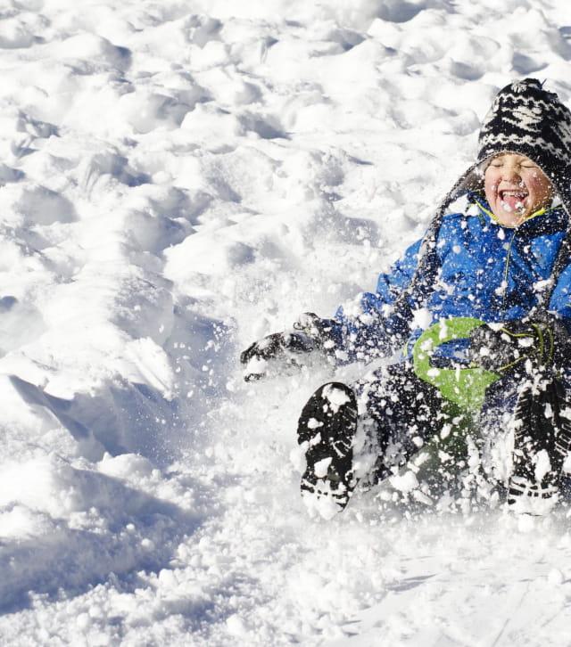 Enfant aspergé de neige en faisant de la luge