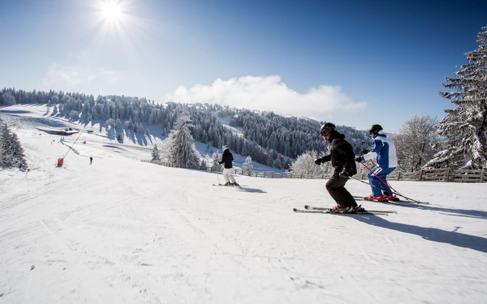 Famille qui dévale les pentes de ski alpin à Métabief