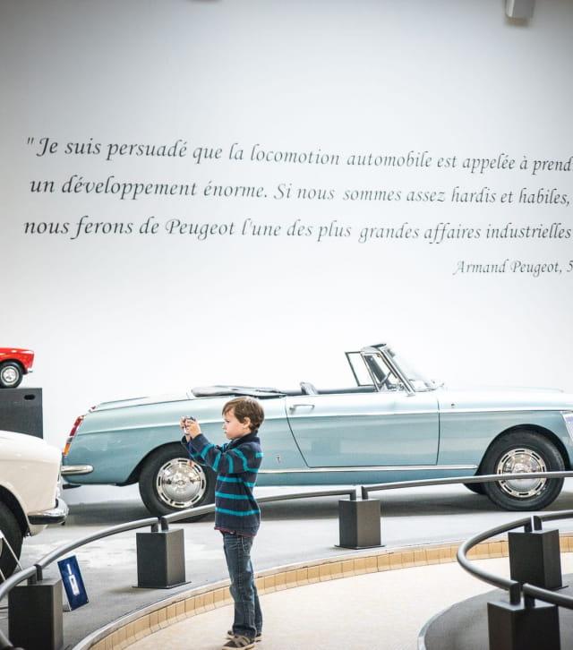 Petit garçon devant une voiture de collection au musée Peugeot